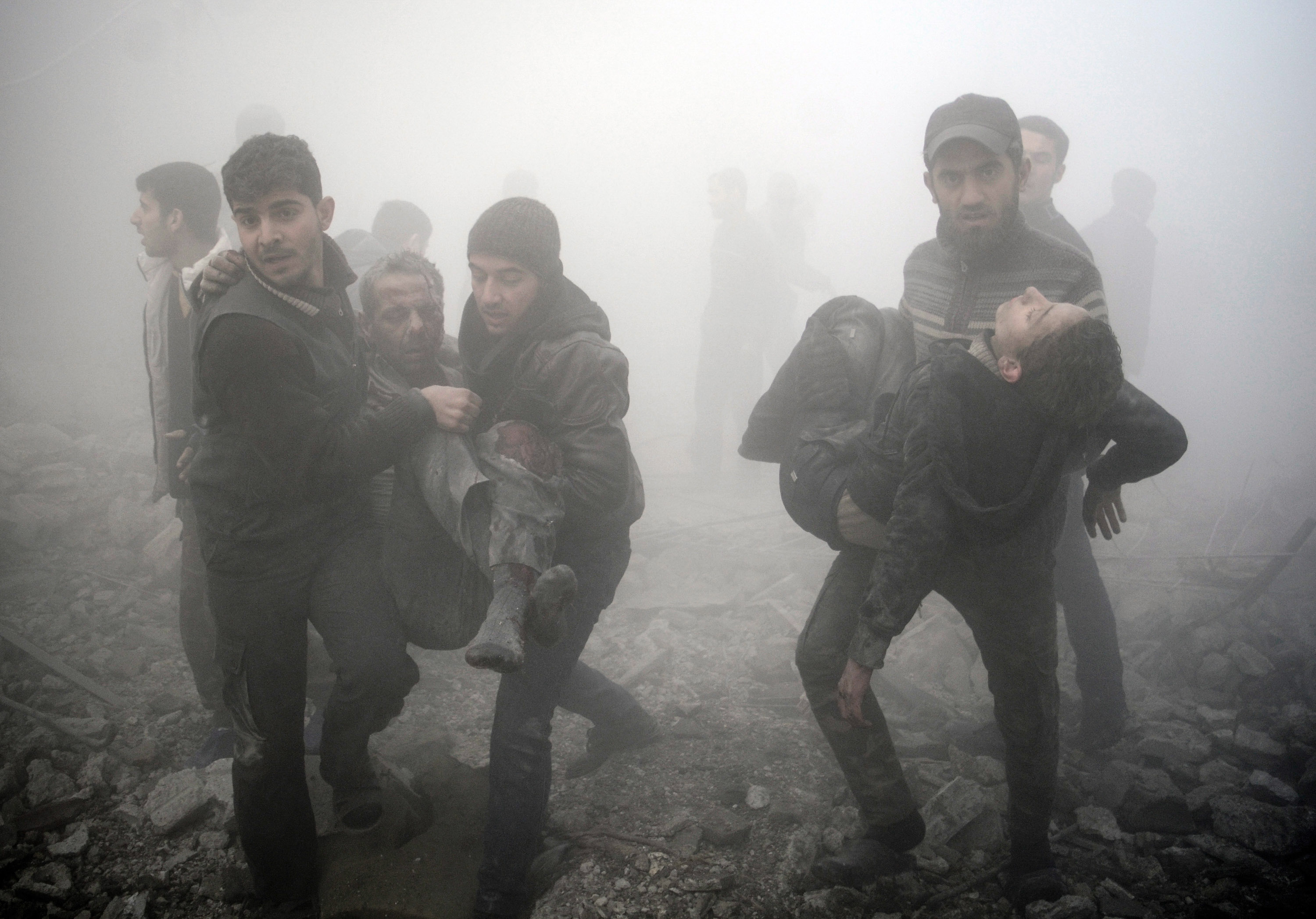 Syrian men carry injured victims following a reported air strike on the besieged rebel-held town of Douma, northeast of the capital Damascus on January 21, 2015. Rebel-held towns such as Douma face frequent aerial and tank bombardment and the siege means food is scarce and medical facilities are ill-equipped to handle either illness or injury. AFP PHOTO / SAMEER AL-DOUMY / AFP PHOTO / - AND SAMEER AL-DOUMY