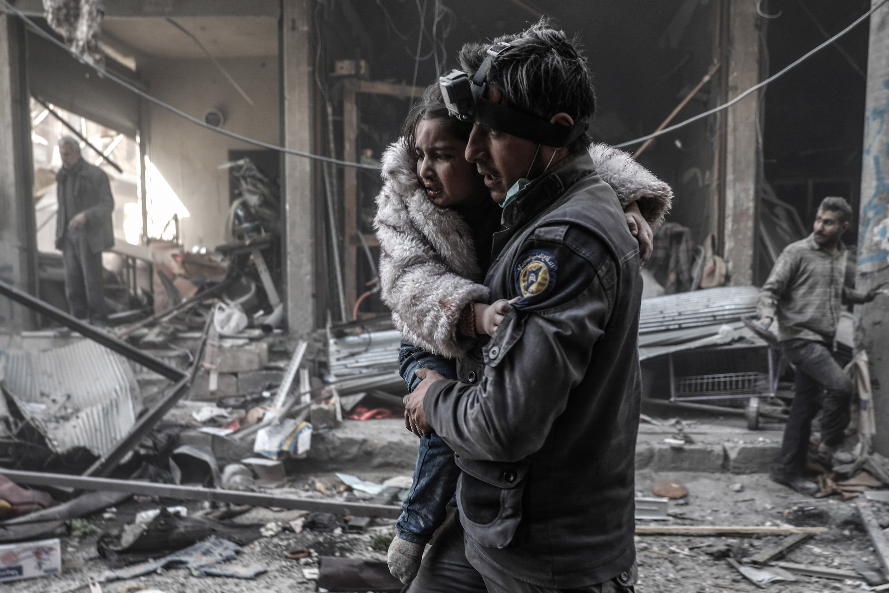 A member of the Syrian Civil Defence volunteers, also known as the White Helmets, carries a wounded girl amid the rubble following reported government airstrike on the rebel-held town of Douma, on the eastern outskirts of the capital Damascus, on February 25, 2017. Syrian regime forces carried out raids on several areas in the country, targeting mainly the besieged town of Douma, causing the deaths of at least 13 civilians, according to Syrian Observatory for Human Rights. The raids continued despite the United Nations confirmation a few days earlier that Moscow formally asked its ally Damascus to stop launching strikes during the Geneva negotiations, which began earlier in the week. / AFP PHOTO / Sameer Al-Doumy